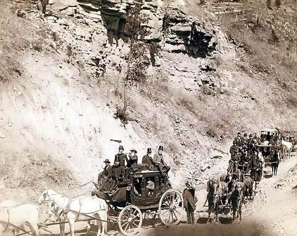 Omaha Board of Trade in Mountains near Deadwood, April 26, 1889. It was created in 1889 by Grabill, John C. H., photographer. The picture presents Procession of stagecoaches loaded with passengers coming down a mountain road.